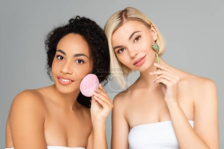 Photo for Young interracial women with jade roller and silicone cleanser looking at camera isolated on grey - Royalty Free Image