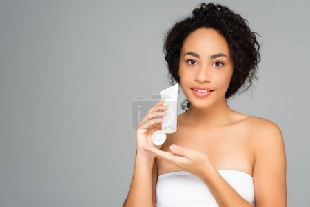 African american woman with perfect skin holding tube with cleansing foam isolated on grey