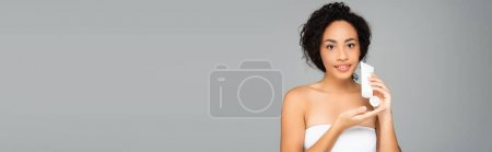 African american woman smiling while holding tube with cosmetic lotion isolated on grey, banner