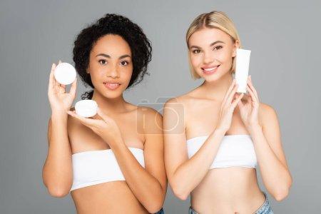 Lächelnde multiethnische Frauen mit Tube und Glas mit Kosmetikcreme isoliert auf grau