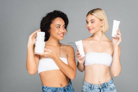 Photo pour Femmes multiethniques se souriant et tenant des pots et des tubes à la crème hydratante isolée sur gris - image libre de droit