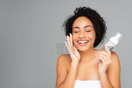 Photo pour Femme américaine africaine joyeuse avec les yeux fermés tenant bouteille de mousse nettoyante isolée sur gris - image libre de droit