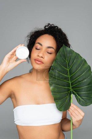 Photo pour Femme afro-américaine en haut blanc tenant crème cosmétique et feuille verte isolée sur gris - image libre de droit