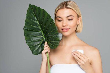 Photo pour Femme blonde aux feuilles tropicales et pot à la crème cosmétique isolé sur gris - image libre de droit