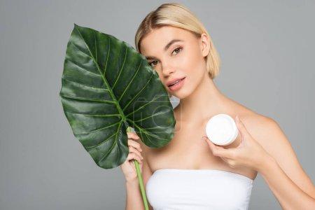 Photo pour Femme avec crème cosmétique et feuille tropicale regardant la caméra isolée sur gris - image libre de droit