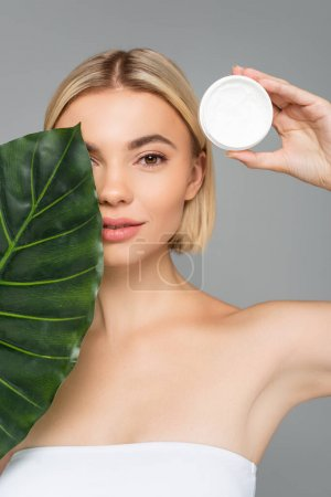 Photo for Blonde woman covering face with tropical leaf and holding cosmetic cream isolated on grey - Royalty Free Image