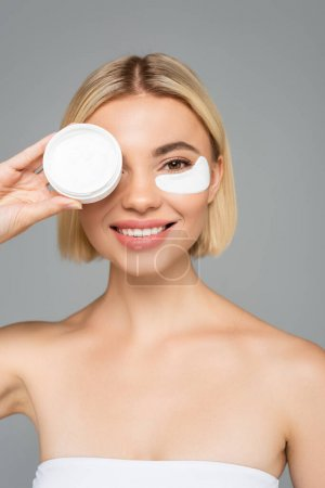 Photo for Smiling blonde woman in eye patch holding cosmetic cream and isolated on grey - Royalty Free Image