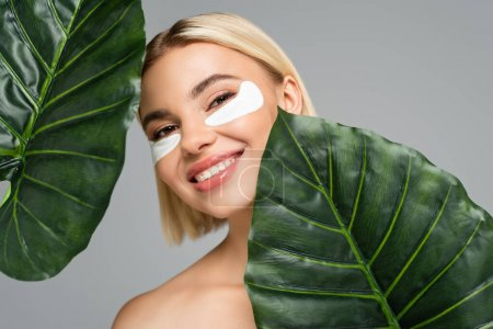 Photo for Young woman with eye patches smiling near green leaves isolated on grey - Royalty Free Image
