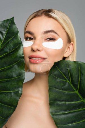 Junge Frau mit perfekter Haut und Augenflecken posiert in der Nähe tropischer Blätter isoliert auf grau