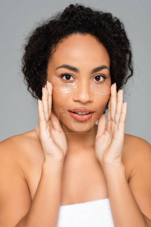 Photo for African american woman with perfect skin applying eye patches isolated on grey - Royalty Free Image