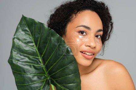 Photo pour Femme afro-américaine souriante en bandeau regardant une caméra près d'une feuille tropicale isolée sur du gris - image libre de droit