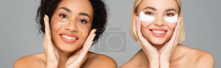 Cheerful multicultural women in eye patches isolated on grey, banner
