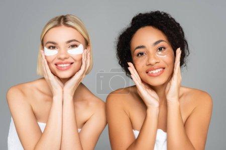 Des femmes souriantes multiethniques dans des bandeaux isolés sur du gris