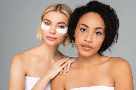 Jeunes femmes multiethniques avec une peau parfaite et des patchs pour les yeux isolés sur gris