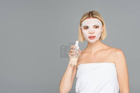 Young woman with sheet mask holding cleansing foam isolated on grey