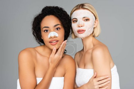 Multiethnic women with cleansing stripe and sheet mask looking at camera isolated on grey