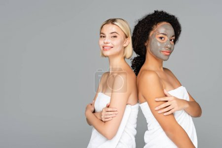 Multicultural women in facial masks and towels looking at camera isolated on grey