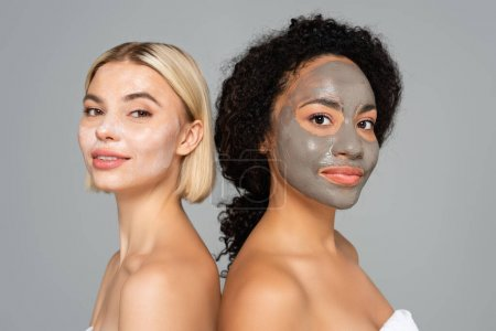 Multiethnic women in facial masks standing back to back isolated on grey