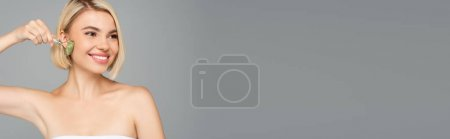 Blonde woman massaging face with jade roller isolated on grey, banner
