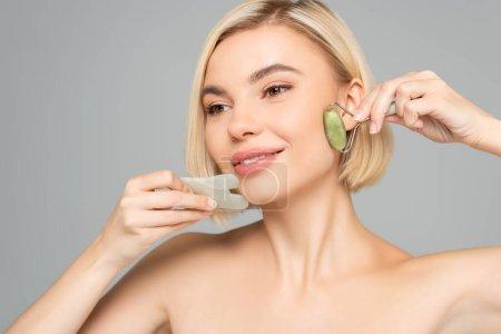 Photo pour Femme blonde avec peau propre massage visage avec gua sha et jade rouleau isolé sur gris - image libre de droit