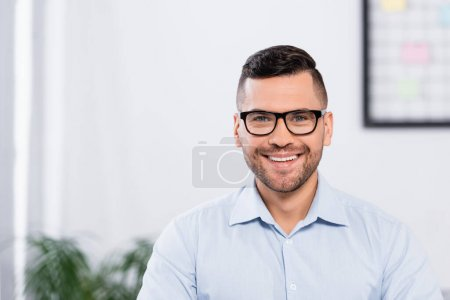happy businessman in glasses smiling while looking at camera