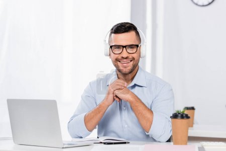 happy businessman in glasses and headphones smiling while looking at camera