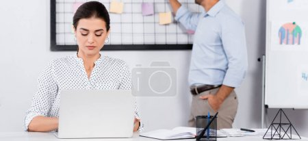 Photo for Businesswoman using laptop near coworker putting sticky notes on board on blurred background, banner - Royalty Free Image