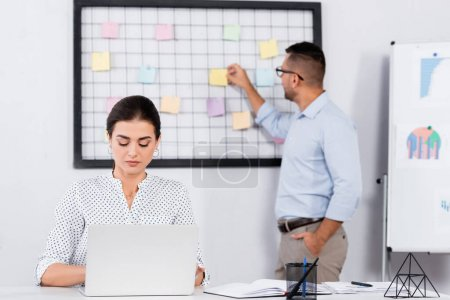 Photo for Businesswoman using laptop near coworker putting sticky notes on board and blurred background - Royalty Free Image