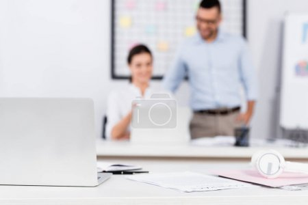 laptop near papers and headphones on desk near business people on blurred background