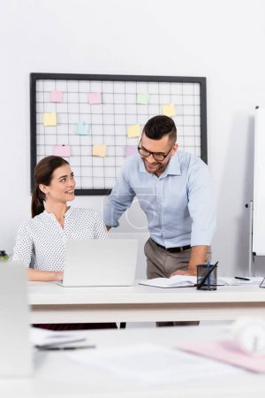 Photo pour Gens d'affaires heureux regardant ordinateur portable au bureau avec premier plan flou - image libre de droit