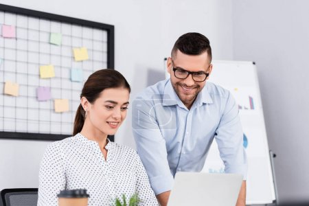 cheerful business people looking at laptop in office with blurred foreground