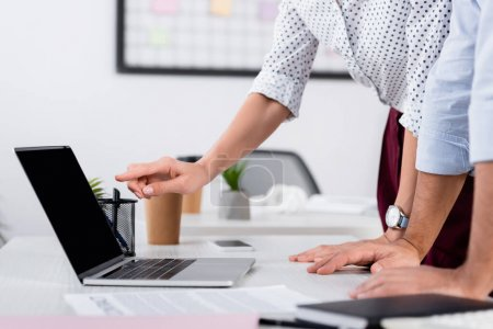 cropped view of businesswoman pointing with finger at laptop with blank screen on desk