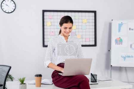 Photo for Cheerful businesswoman looking at laptop and sitting on desk - Royalty Free Image