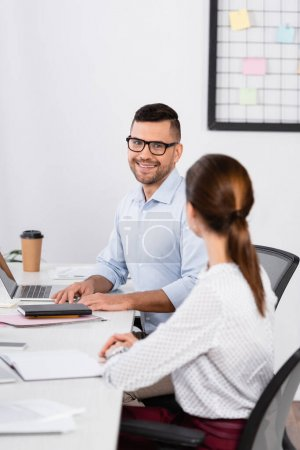 cheerful businessman in glasses looking at businesswoman sitting at desk on blurred foreground