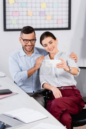 happy businesswoman taking selfie with coworker in glasses