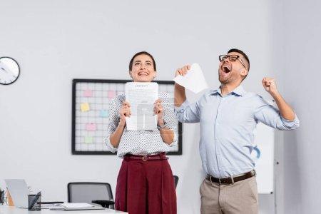 gente de negocios emocionada sosteniendo documentos con contrato en la oficina