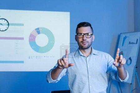 Photo pour Homme d'affaires dans des lunettes pointant avec les doigts près des cartes et des graphiques - image libre de droit