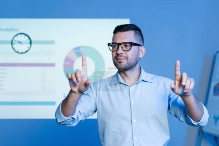 Photo for Businessman in glasses pointing with fingers near charts and graphs on wall - Royalty Free Image
