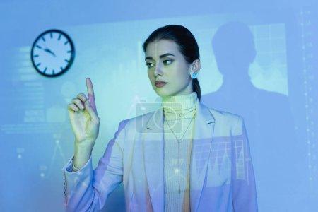 Photo pour Femme d'affaires pointant du doigt près des graphiques numériques dans le bureau - image libre de droit