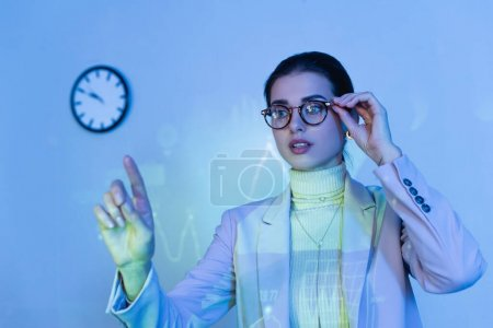 Photo for Businesswoman in suit adjusting glasses and pointing with finger near digital graphs - Royalty Free Image