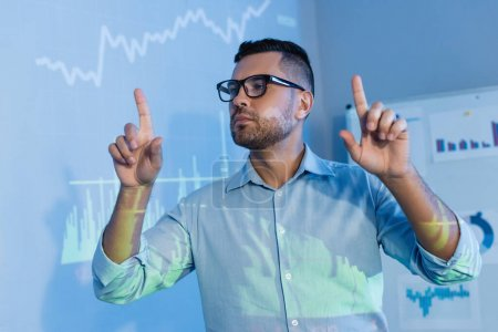businessman in glasses pointing with fingers near digital graphs in office