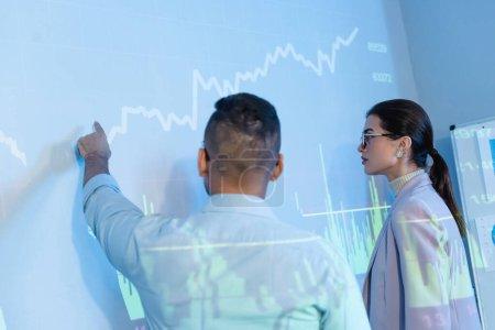 Photo pour Homme d'affaires pointant du doigt au mur avec des graphiques numériques proche collègue - image libre de droit