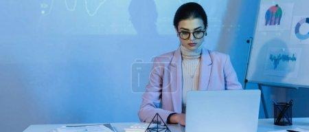 Geschäftsfrau in Brille mit Laptop nahe digitaler Graphik an Wand, Banner