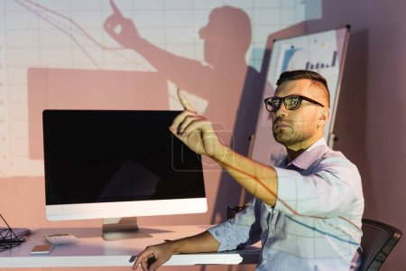 Photo for Businessman in glasses pointing with finger near computer monitor with blank screen - Royalty Free Image