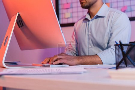 Photo for Cropped view of businessman typing on computer keyboard near monitor - Royalty Free Image