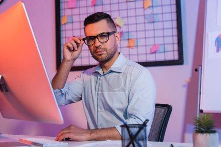 homme d'affaires réglage des lunettes près du clavier de l'ordinateur et moniteur