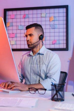 opérateur en tapant casque sur le clavier de l'ordinateur et en regardant le moniteur