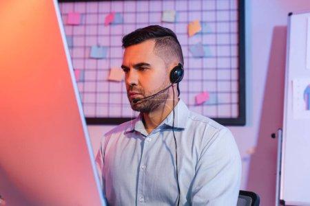 Photo pour Opérateur dans casque regardant moniteur d'ordinateur - image libre de droit