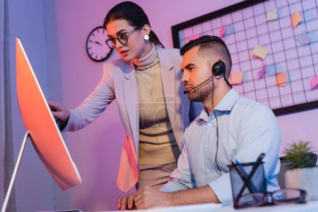 operator in headset looking at computer monitor near businesswoman in office