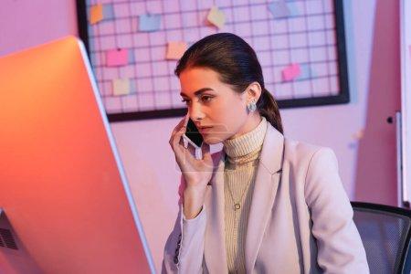 mujer de negocios hablando en el teléfono inteligente y mirando el monitor de computadora en la oficina